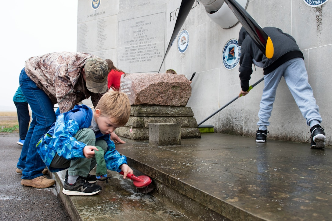 Joshua Dunmire scrubs the 355th Fighter Group Steeple Morden Memorial in Steeple Morden, England, during Operation TORCH-2020 memorial cleanup August 15, 2020. U.S. Africa Command Directorate for Intelligence at RAF Molesworth partnered with the American Battle Monuments Commission to host Operation TORCH-2020, where over 50 military members and their families, U.K. nationals and Boy Scout Troop #245, cleaned six WWII memorial sites to preserve American service member legacies and promote an appreciation of past American heroes among present-day USAFRICOM workforce and families. (U.S. Air Force Photo by Airman 1st Class Jennifer Zima)