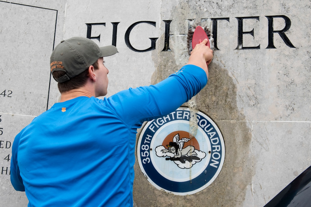 U.S. Navy Petty Officer 2nd Class Sebastian Botero, U.S. Africa Command Directorate for Intelligence at RAF Molesworth technician, scrubs the 355th Fighter Group Steeple Morden Memorial in Steeple Morden, England, during Operation TORCH-2020 memorial cleanup August 15, 2020. U.S. Africa Command Directorate for Intelligence at RAF Molesworth partnered with the American Battle Monuments Commission to host Operation TORCH-2020, where over 50 military members and their families, U.K. nationals and Boy Scout Troop #245, cleaned six WWII memorial sites to preserve American service member legacies and promote an appreciation of past American heroes among present-day USAFRICOM workforce and families. (U.S. Air Force Photo by Airman 1st Class Jennifer Zima)