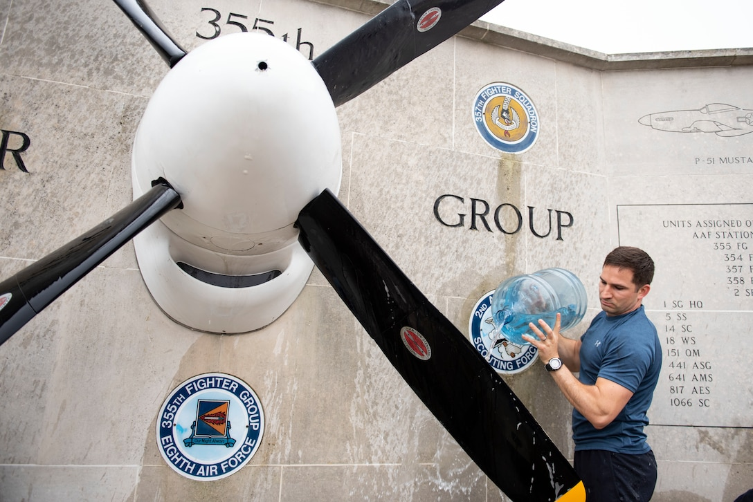 U.S. Army Capt. Chris Philhower, U.S. Africa Command Directorate for Intelligence at RAF Molesworthtechnician, cleans the 355th Fighter Group Steeple Morden Memorial in Steeple Morden, England, during Operation TORCH-2020 memorial cleanup August 15, 2020. U.S. Africa Command Directorate for Intelligence at RAF Molesworth partnered with the American Battle Monuments Commission to host Operation TORCH-2020, where over 50 military members and their families, U.K. nationals and Boy Scout Troop #245, cleaned six WWII memorial sites to preserve American service member legacies and promote an appreciation of past American heroes among present-day USAFRICOM workforce and families. (U.S. Air Force Photo by Airman 1st Class Jennifer Zima)