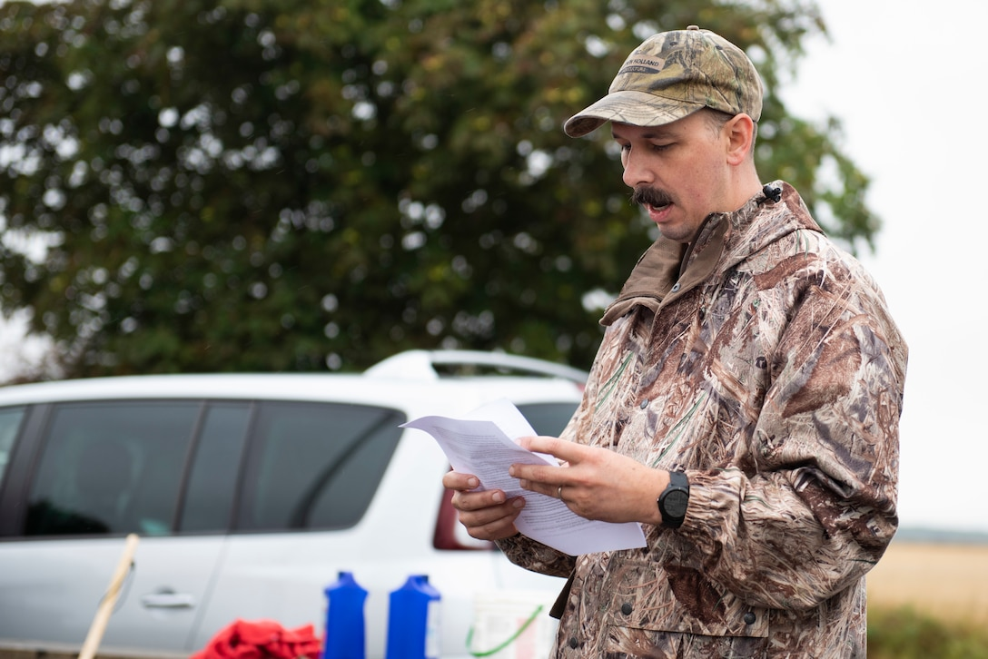 U.S. Air Force Master Sgt. Aaron Beil, U.S. Africa Command Directorate for Intelligence at RAF Molesworth technician, reads the history of the 355th Fighter Group Steeple Morden Memorial in Steeple Morden, England, during Operation TORCH-2020 memorial cleanup August 15, 2020. U.S. Africa Command Directorate for Intelligence at RAF Molesworth partnered with the American Battle Monuments Commission to host Operation TORCH-2020, where over 50 military members and their families, U.K. nationals and Boy Scout Troop #245, cleaned six WWII memorial sites to preserve American service member legacies and promote an appreciation of past American heroes among present-day USAFRICOM workforce and families. (U.S. Air Force Photo by Airman 1st Class Jennifer Zima)