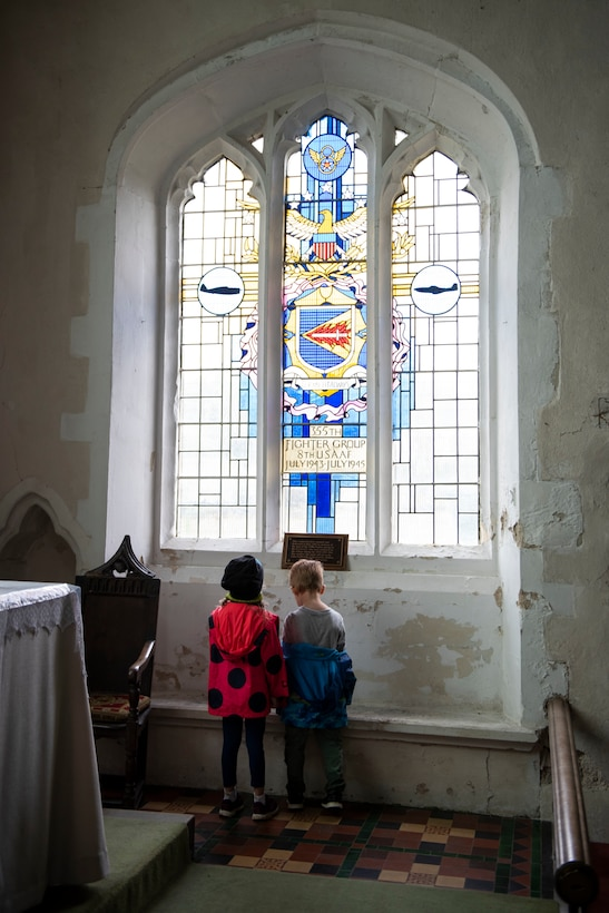 Kaitlyn and Joshua Dunmire look at the memorial window at St. Catherine's Church in Litlington, England, August 15, 2020. U.S. Africa Command Directorate for Intelligence at RAF Molesworth partnered with the American Battle Monuments Commission to host Operation TORCH-2020, where over 50 military members and their families, U.K. nationals and Boy Scout Troop #245, cleaned six WWII memorial sites to preserve American service member legacies and promote an appreciation of past American heroes among present-day USAFRICOM workforce and families. (U.S. Air Force Photo by Airman 1st Class Jennifer Zima)