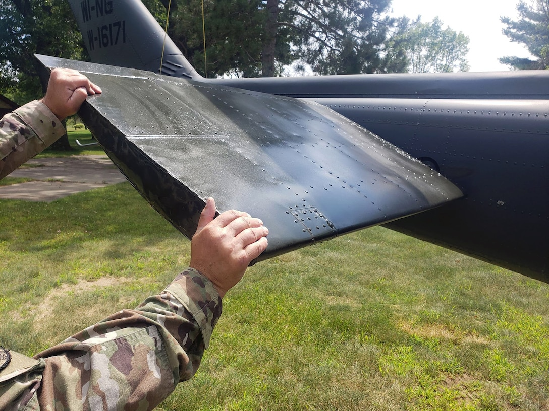 An Air National Guard crew chief assigned to 132nd Wing, Des Moines, Iowa, holds tail of Huey 66-16171