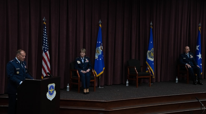 Maj. Gen. Bibb delivers remarks at podium while Gen. Maryanne Miller and Maj. Gen. Barrett view from the stage.