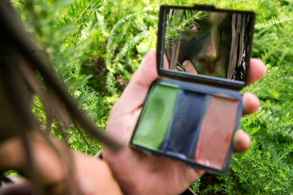 A Marine looks at himself in the mirror of a camouflage paint compact.