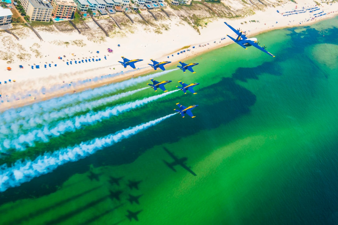 Planes fly in formation over a beach.