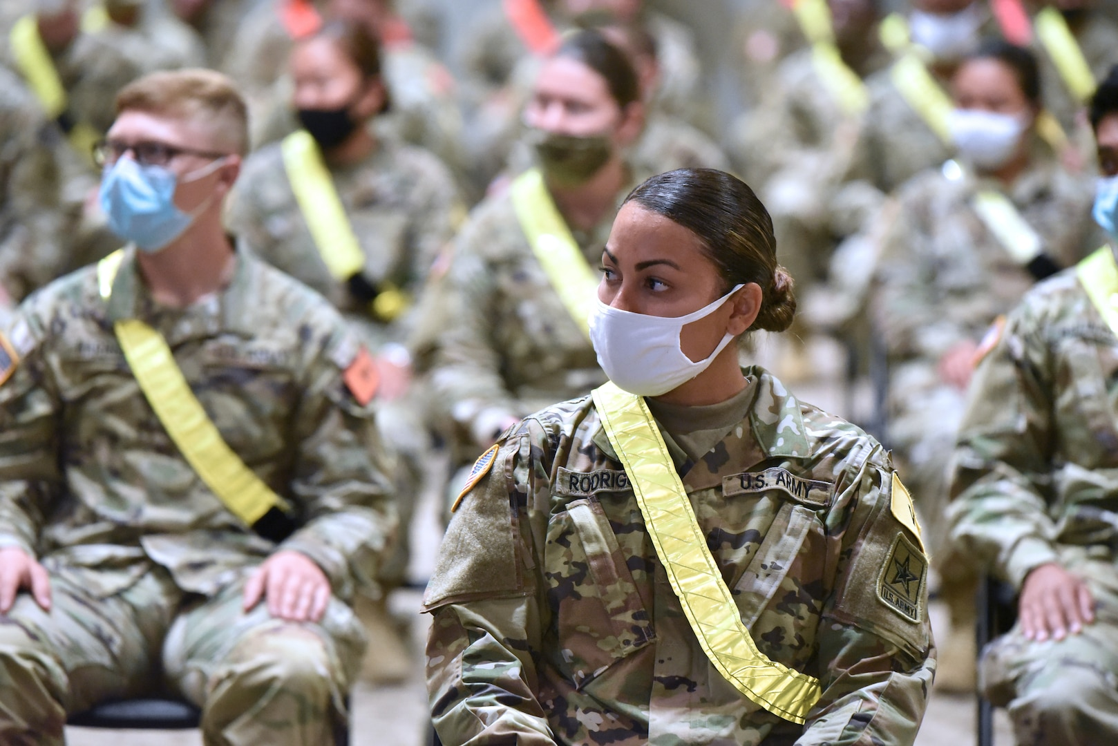 Soldiers seated wearing face masks.