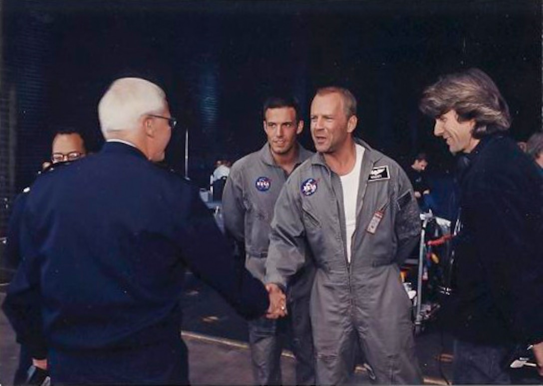 """Actors Ben Affleck and Bruce Willis and director Michael Bay meet Maj. Gen. (retired) Richard Engel, then commander of the Air Force Test Center, during filming of the movie """"Armageddon"""" at Edwards Air Force Base, California. (Photo courtesy of Air Force Test Center History Office)"""