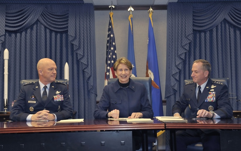 A civilian woman sits between two Air Force generals after signing official documents.