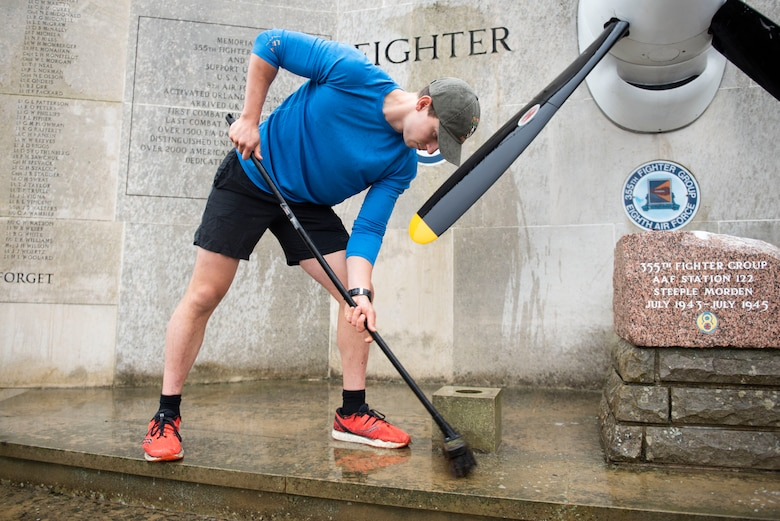 U.S. Navy Petty Officer 2nd Class Sebastian Botero, U.S. Africa Command Directorate for Intelligence at RAF Molesworthtechnician, scrubs the 355th Fighter Group Steeple Morden Memorial in Steeple Morden, England, during Operation TORCH-2020 memorial cleanup August 15, 2020. U.S. Africa Command Directorate for Intelligence at RAF Molesworth partnered with the American Battle Monuments Commission to host Operation TORCH-2020, where over 50 military members and their families, U.K. nationals and Boy Scout Troop #245, cleaned six WWII memorial sites to preserve American service member legacies and promote an appreciation of past American heroes among present-day USAFRICOM workforce and families. (U.S. Air Force Photo by Airman 1st Class Jennifer Zima)