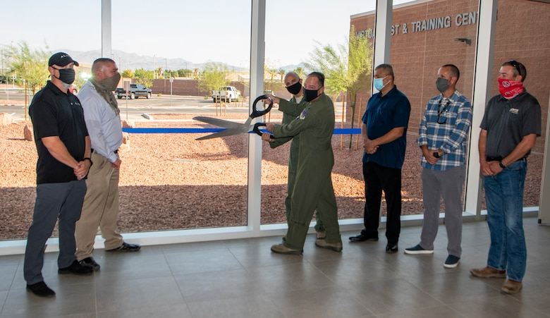 Airmen and civilians stand outside the  grad opening of the U.S. Warfare Center Virtual Test and Training Center to cut a ribbon.