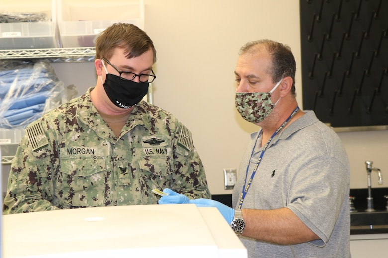 A Navy Corpsman in uniform listens to a civilian employee speak in a hospital lab.