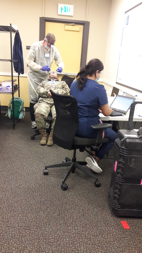 An unidentified Airman is receiving a dental exam as staff assistant records the notes and maintaining social distancing.