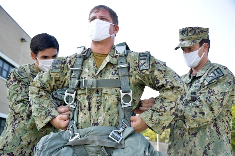 JOINT BASE MCGUIRE-DIX-LAKEHURST, N.J. – Chief Nicholas Clark, a leading chief petty officer with U.S. Navy Explosive Ordnance Disposal Mobile Unit 12 (EODMU-12), tightens the harness on an MC-6 parachute system during an airborne fresher course here on Aug. 12, 2020. Members of the EODMU-12 interacted with U.S. Army Reserve Jumpmasters and paratroopers during training in order to maintain proficiency in conducting joint missions.