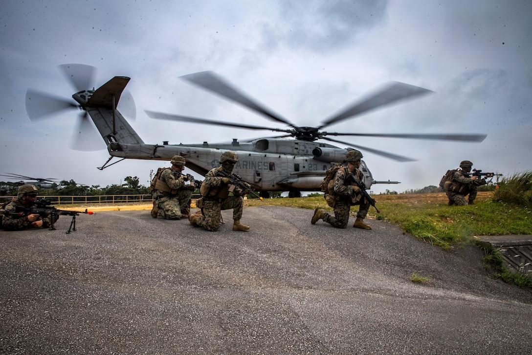 U.S. Marines post security around a CH-53E Super Stallion at the Jungle Warfare Training Center, Okinawa, Japan, Aug. 6.