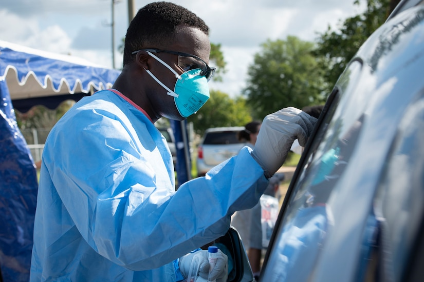 An airman wearing personal protective equipment administers a COVID-19 test to a person in their car.
