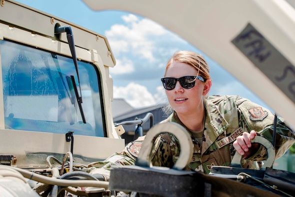 Air Force Reserve Staff Sgt. Tiah Phillips, inspects the engine of a Humvee Aug. 2, 2020, at Little Rock Air Force Base, Ark. Earlier in her career she cross-trained into vehicle operations, where she deployed to Kuwait and Iraq in 2011. Phillips drove dozens of convoy missions in tractor trucks, bringing back heavy equipment from forward operating bases as operations were drawn down. (U.S. Air Force Reserve photo by Maj. Ashley Walker)
