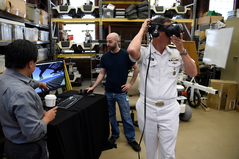 A sailor and two other men work with artificial intelligence devices.