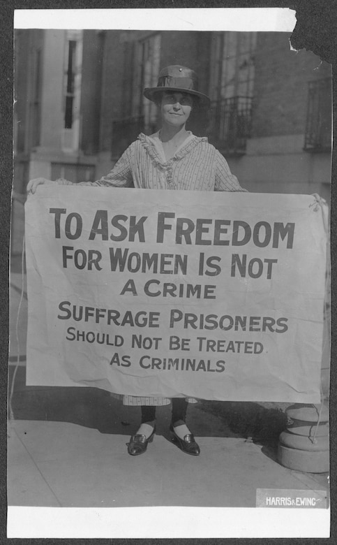 photograph from 1917 of woman during womans suffrage movement named Mary Winsor holding up a sign in protest. Sign reads as following   To ask freedom for women in not a crime