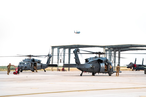 U.S. Air Force F-15E strikes eagles take-off while three HH-60G Pave Hawks standby Aug. 17, 2020, at Mountain Home Air Force Base, Idaho. Both airframes are participating in Gunfighter Flag 20-1, which aims to hone joint and multi-national armed forces to become more agile and lethal. (U.S. Air Force photo by Airman 1st Class Andrew Kobialka)