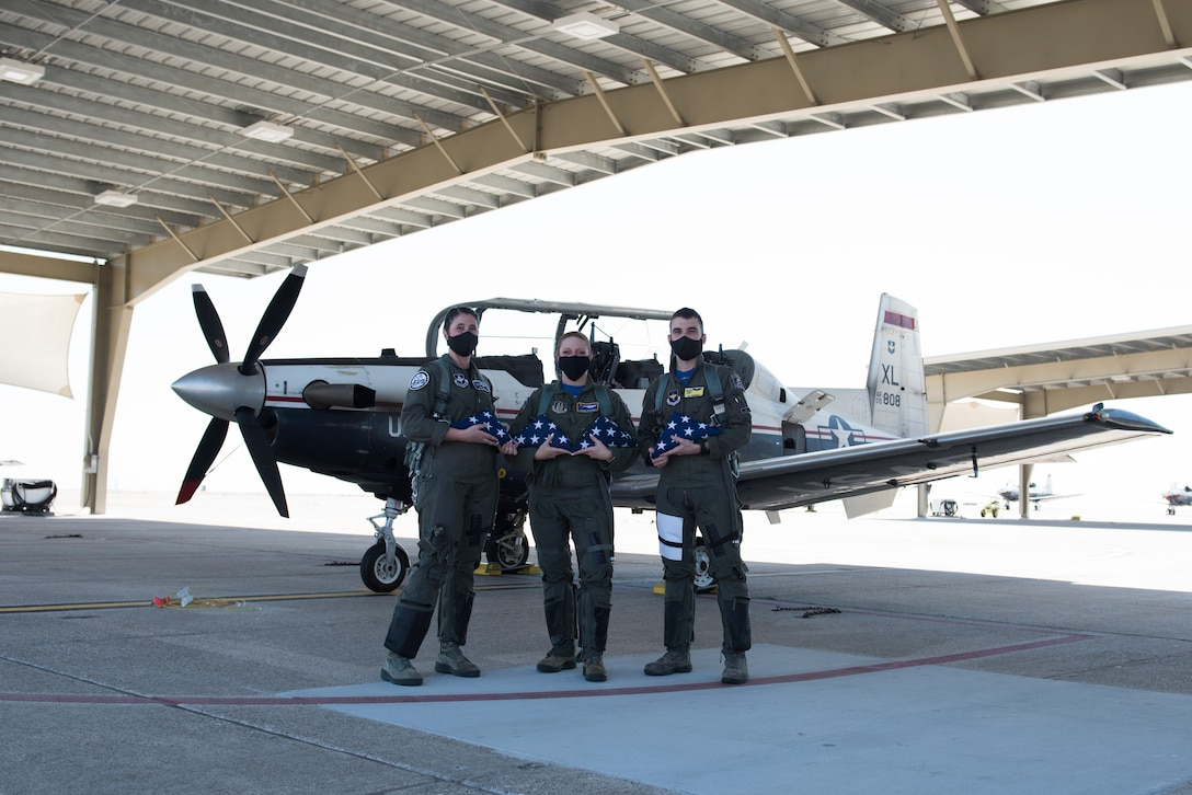First Lt. April Wilcox, 85th Flying Training Squadron executive officer, Maj. Camber Governski, 96th FTS T-6A Texan II chief pilot, and 1st Lt. Will Friedman 85th FTS A-flight scheduler, pose in front of a T-6 on Aug. 14, 2020 at Laughlin Air Force Base, Texas, with the flags they are to fly for the families of the U.S. Customs and Border Protection service members who were lost to COVID-19. As they flew the flags, they practiced flying in formation to increase proficiency in order to train the student pilots more effectively. (U.S. Air Force photo by Senior Airman Anne McCready)