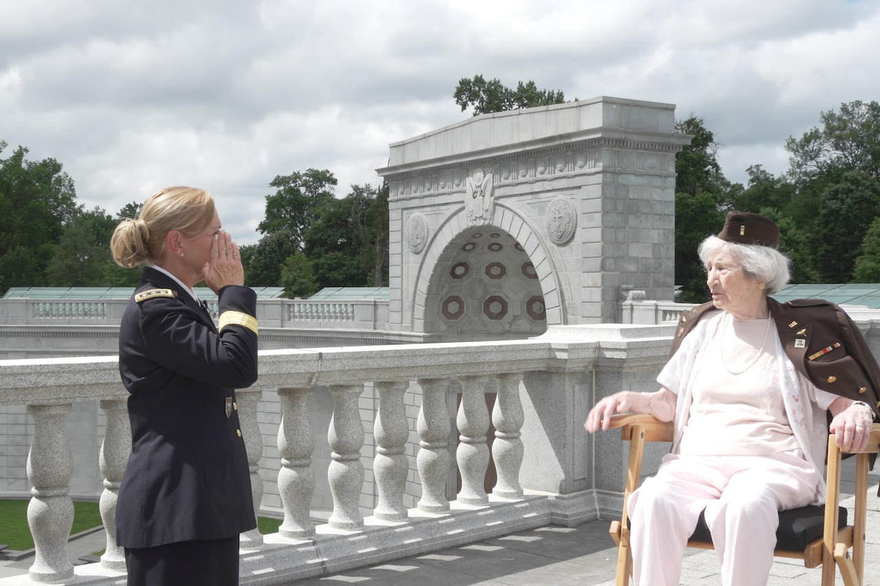 A woman in an Army uniform salutes a female World War II veteran.