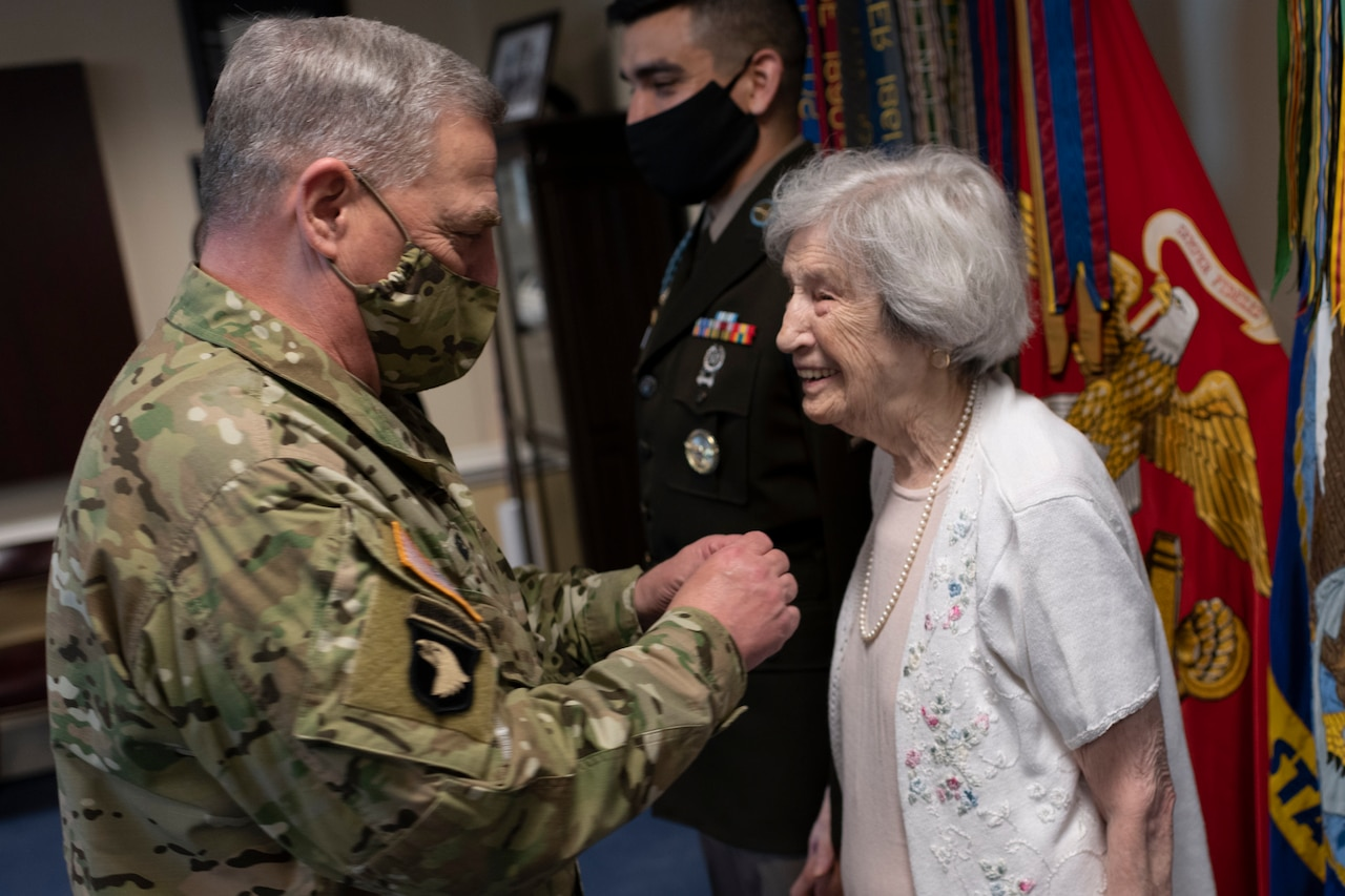A general wearing a face mask presents a medal to a smiling civilian woman.