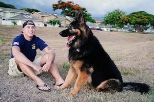 U.S. Navy Sonar Technicians Submarine 1st Class Christopher Carr, Naval Submarine Training Command Pacific instructor, relaxes after playtime with his dog, Zeus, in Honolulu, Hawaii, Aug. 12, 2020. Zeus is a 110-pound Shiloh Shepherd who was trained by a police force K9 trainer. (U.S. Air Force photo by Airman 1st Class Erin Baxter)