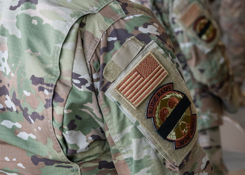 A picture of uniform personnel wearing a modified unit patch to commemorate a fallen Airman.