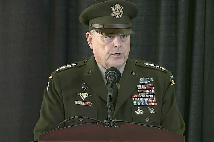 A man in a U.S. Army uniform stands at a microphone on a lectern.