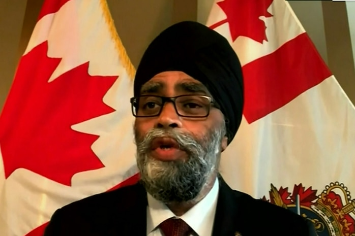 A man standing in front of two Canadian flags is speaking.