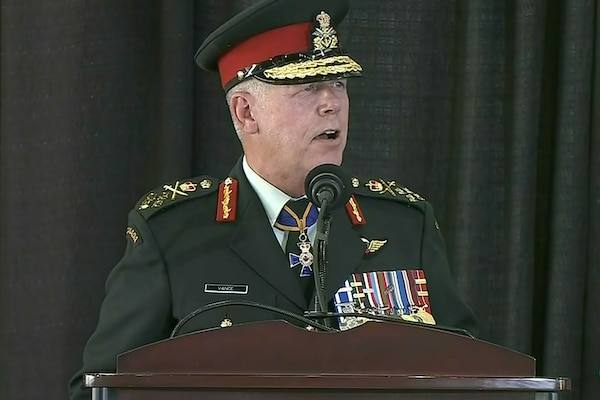 A man in a Canadian uniform stands at a microphone on a lectern.