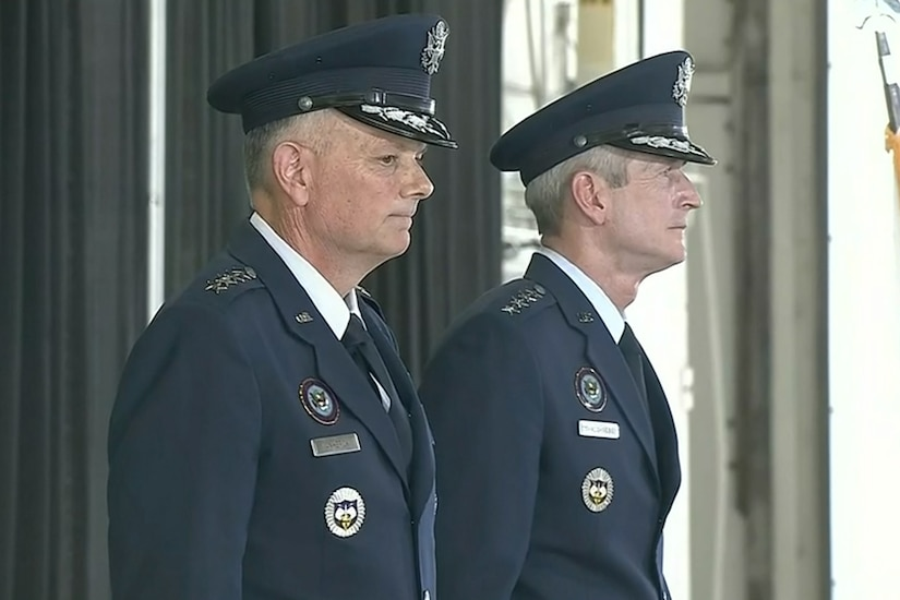Two men in military uniform stand at attention.