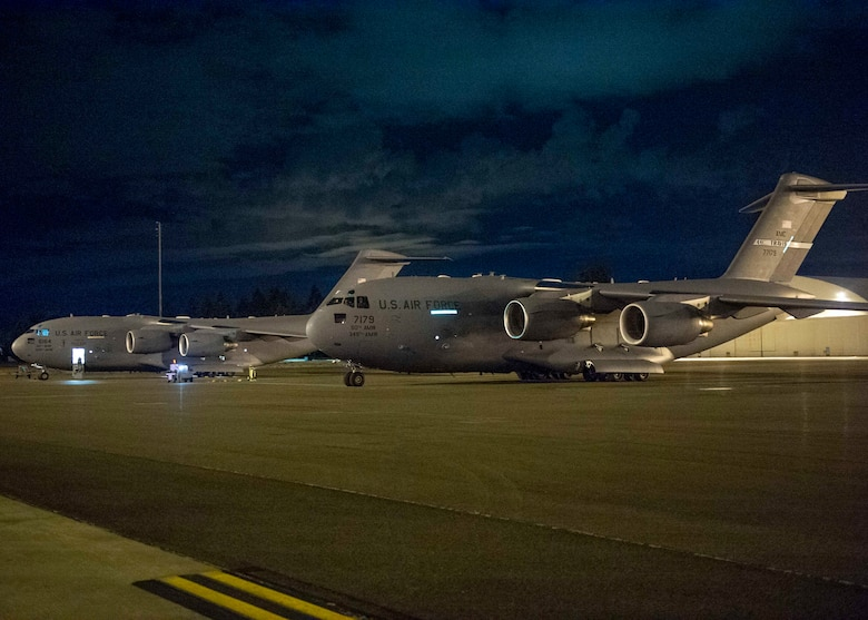 Two C-17 Globemaster III aircraft from Travis Air Force Base, Calif., sit on the flightline at Joint Base Lewis-McChord, Wash., Aug. 20, 2020. Airmen from Team McChord coordinated arrival and transportation for air crews of four Travis AFB C-17s after they evacuated due to fires near Fairfield and Vacaville, Calif. (U.S. Air Force photo by Senior Airman Sara Hoerichs)