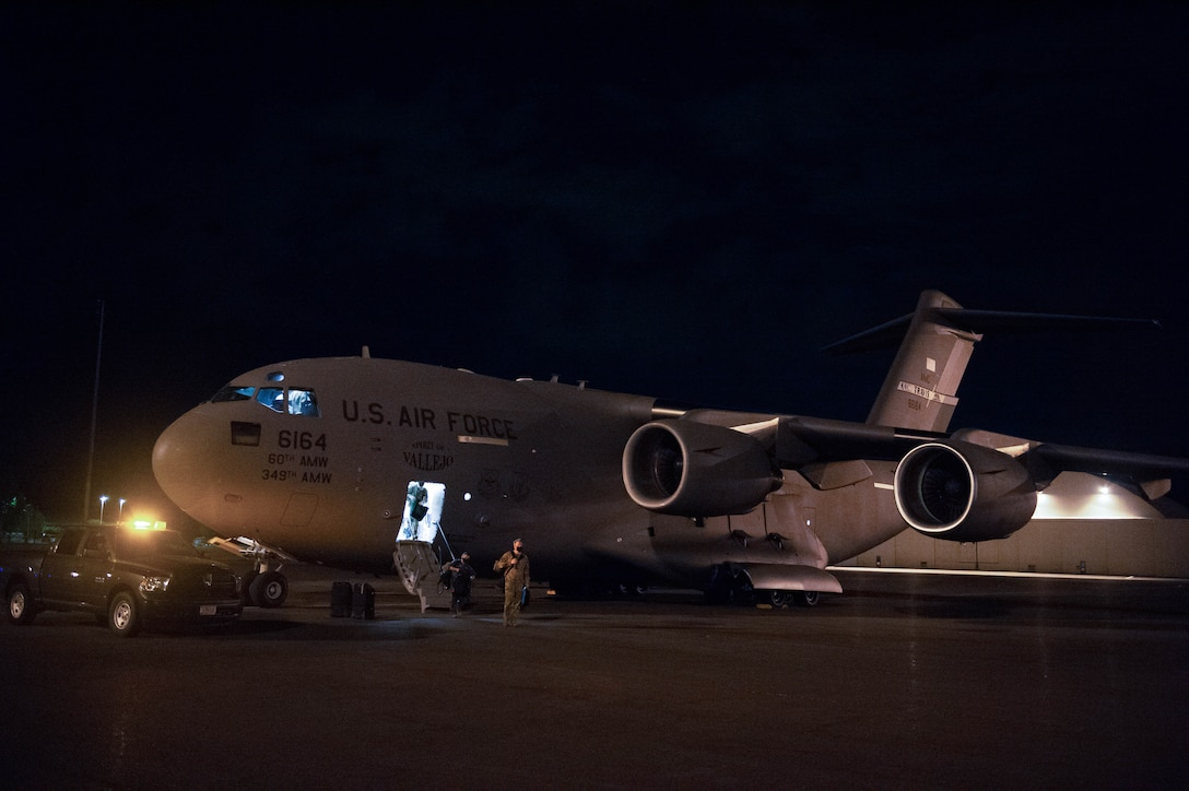 A C-17 Globemaster III air crew from Travis Air Force Base, Calif., disembarks on the McChord Field flightline at Joint Base Lewis-McChord, Wash., Aug. 20, 2020. Four C-17s from Travis AFB evacuated to JBLM after the Travis AFB installation commander ordered an emergency evacuation of non-mission essential personnel due to fires near Fairfield and Vacaville, Calif. (U.S. Air Force photo by Senior Airman Sara Hoerichs)