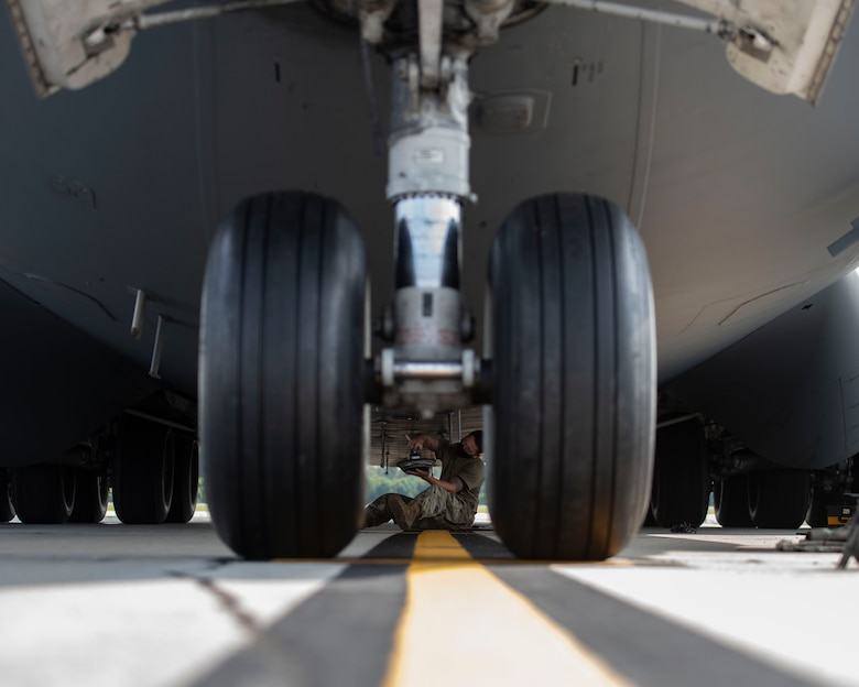 Staff Sgt. Brandon Whitley, an aerospace mechanic assigned to the 437th Aircraft Maintenance Squadron, connects an anti-collision light to the bottom of a C-17 Globemaster III at Joint Base Charleston, S.C., Aug. 18, 2020. The 437th AMXS inspects, services, and maintains the assigned C-17 aircraft at Joint Base Charleston.