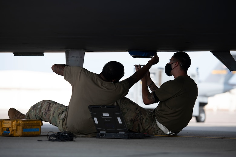 Tech. Sgt. Joie Lucas and Staff Sgt. Brandon Whitley, aerospace mechanics assigned to the 437th Aircraft Maintenance Squadron, install an anti-collision light to the bottom of a C-17 Globemaster III at Joint Base Charleston, S.C., Aug. 18, 2020. The 437th AMXS inspects, services, and maintains the assigned C-17 aircraft at Joint Base Charleston.