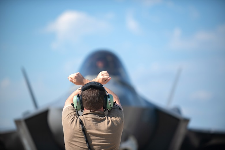 """A crew chief assigned to the 158th Maintenance Group, Vermont Air National Guard, marshals an F-35A Lightning II at Northern Lightning, a training exercise held annually at Volk Field, Wisc., Aug. 13, 2020. Lt. Col. John """"Rocky"""" MacRae, assigned to the 134th Fighter Squadron, Vermont Air National Guard, was piloting this Tail 5279, which achieved the thousandth sortie milestone for the Green Mountain Boys. (U.S. Air National Guard photo by Ms. Julie M. Shea)"""