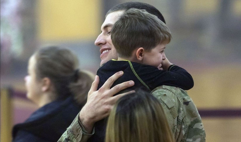 A soldier hugs a small child.
