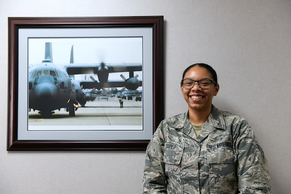 An Airman poses for a photo after receiving an award