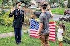 Future Soldier Ronald Kaszian Sauerbrey receives his Oath of Enlistment from company commander Capt. Mehmet Bahadir, while his younger siblings hold the American flag behind them.