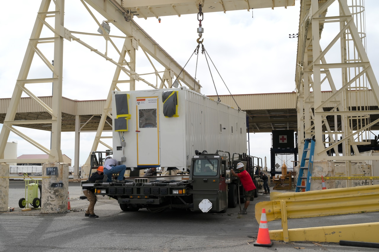Airmen use a crane to load a negatively pressurized conex onto an awaiting vehicle.