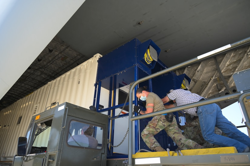 Airmen push a negatiely pressurized conex into a C-17 Globemaster III.