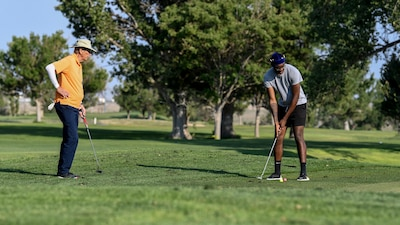 An Airman and retiree golf.