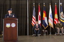 A military officer speaks from behind a dias.