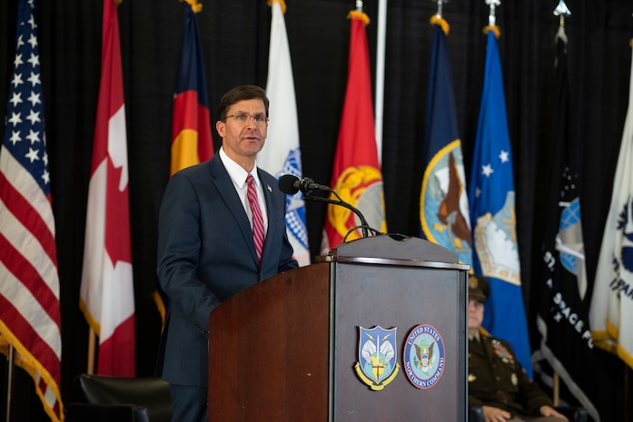 Defense Secretary Dr. Mark T. Esper speaks  from a stage.