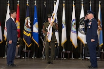 Three men stand on stage with the one in the middle holding a flag.