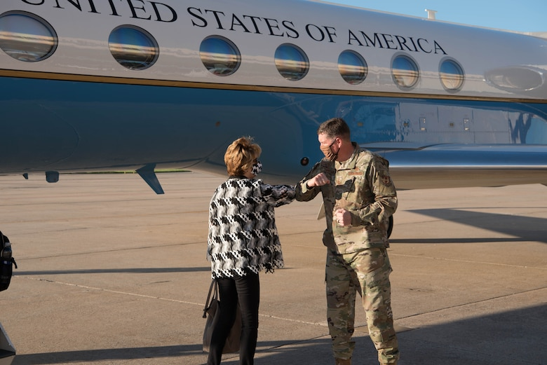 Hon. Lord touching elbows with Lt. Gen. Kirkland in front of aircraft.