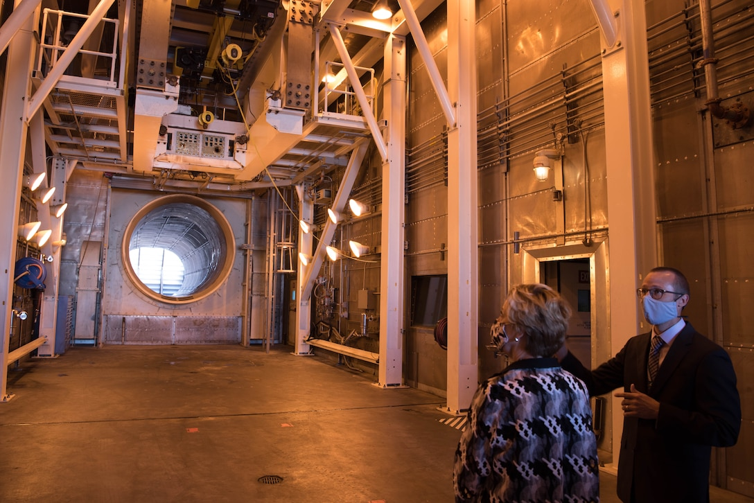 Two people looking at empty jet engine test cell.
