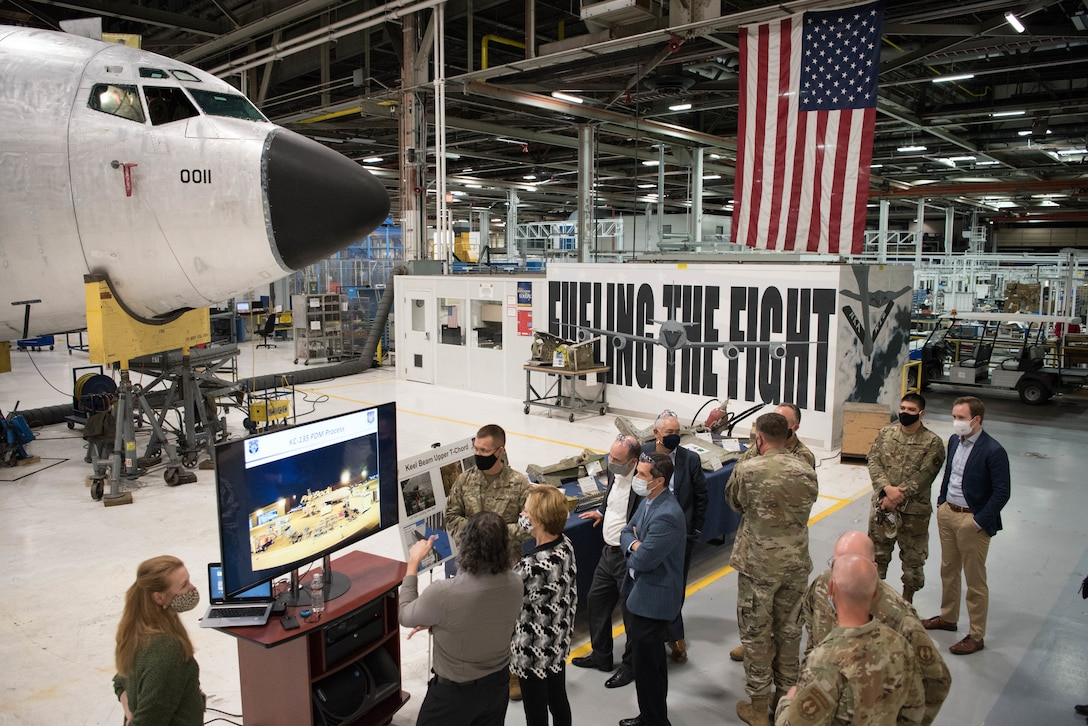 Group of Airmen and Civilians looking at TV with aircraft undergoing maintenance in background.
