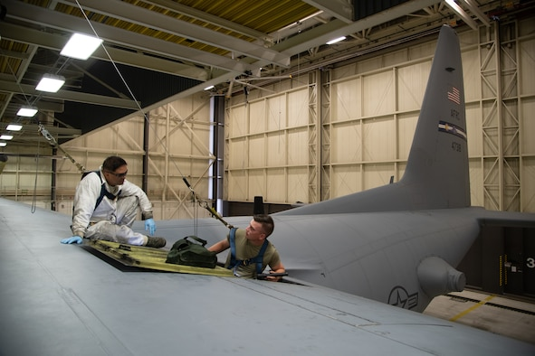 Two Airman sit on top of a C-130 wing inside of a hangar and connect electrical components inside of a panel.
